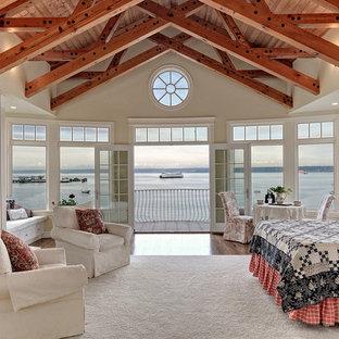 Cette photo montre une grand chambre parentale bord de mer avec un sol en bois brun, une cheminée standard, un manteau de cheminée en métal et un mur beige.