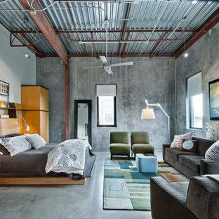 Bild på ett industriellt huvudsovrum, med grå väggar och betonggolv