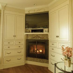 Imagen de habitación de invitados actual, grande, con paredes beige, suelo de madera en tonos medios, chimenea de esquina y marco de chimenea de baldosas y/o azulejos