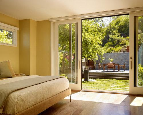 Minimalist medium tone wood floor and beige floor bedroom photo in San Francisco with beige walls & Disappearing Patio Doors | Houzz pezcame.com