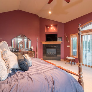 Foto de dormitorio principal, moderno, extra grande, con paredes rojas, moqueta, chimenea tradicional y marco de chimenea de piedra