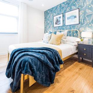 Cette photo montre une chambre tendance avec un mur bleu, un sol en bois clair et un sol beige.