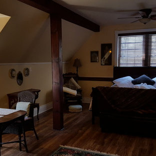 This is an example of a large country loft-style bedroom in Toronto with beige walls, a corner fireplace and a wood fireplace surround.