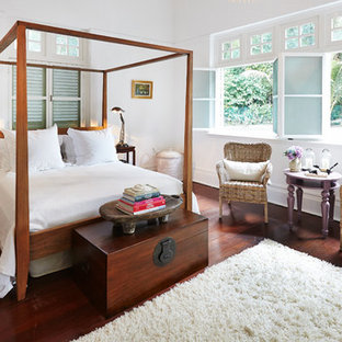 Example of a mid-sized island style medium tone wood floor and red floor bedroom design in London with white walls