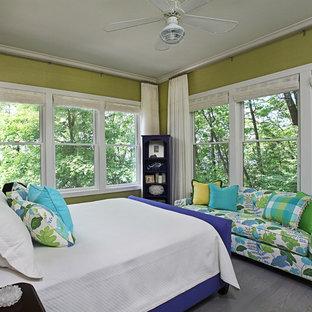 Imagen de dormitorio principal, tropical, grande, sin chimenea, con paredes verdes, suelo de madera en tonos medios y suelo gris