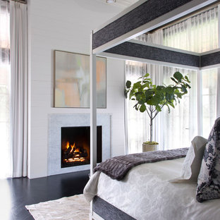 Transitional bedroom in Denver with white walls, dark hardwood floors, a standard fireplace and black floor.