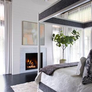 Modelo de dormitorio tradicional renovado con paredes blancas, suelo de madera oscura, chimenea tradicional y suelo negro