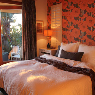 This is an example of an eclectic bedroom in San Diego with orange walls.