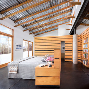 Inspiration for a mid-sized industrial master bedroom in Denver with white walls, concrete floors and black floor.