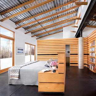 Inspiration för mellanstora industriella huvudsovrum, med vita väggar, betonggolv och svart golv