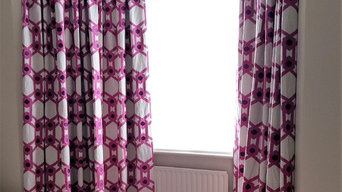 Colourful embroidered curtains on bent track