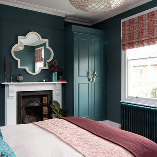 Design ideas for a medium sized bohemian guest bedroom in London with blue walls, a standard fireplace and a metal fireplace surround.