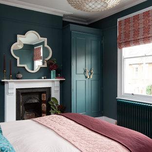ロンドンの中くらいのエクレクティックスタイルのおしゃれな客用寝室 (青い壁、標準型暖炉、金属の暖炉まわり)