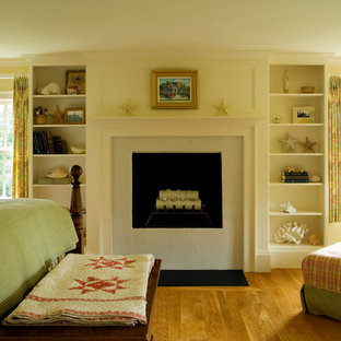 Imagen de dormitorio principal, clásico, grande, con paredes beige, suelo de madera en tonos medios, estufa de leña y marco de chimenea de piedra