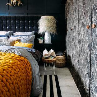 Modelo de dormitorio principal, bohemio, pequeño, sin chimenea, con paredes negras, suelo laminado y suelo gris