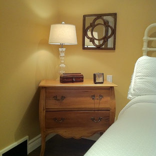 This is an example of a mid-sized traditional master bedroom in Calgary with beige walls and medium hardwood floors.