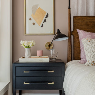 Example of a transitional medium tone wood floor and brown floor bedroom design in Boston with pink walls