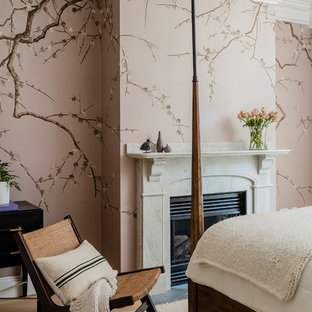 Example of a transitional medium tone wood floor and brown floor bedroom design in Boston with pink walls and a standard fireplace