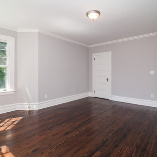 Photo of a large victorian master bedroom in New York with beige walls, dark hardwood floors, no fireplace and brown floor.