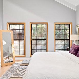 Ejemplo de dormitorio principal, tradicional renovado, grande, con paredes grises, suelo de madera clara, chimenea tradicional, marco de chimenea de baldosas y/o azulejos y suelo beige
