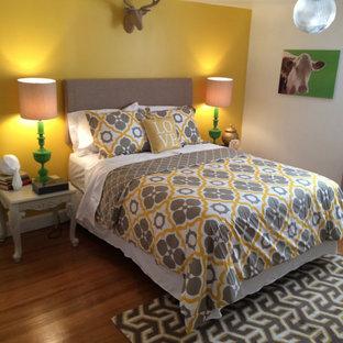 Imagen de habitación de invitados clásica renovada, de tamaño medio, sin chimenea, con paredes amarillas, suelo de madera en tonos medios y suelo marrón