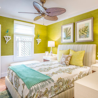 This is an example of a mid-sized beach style master bedroom in Miami with yellow walls, light hardwood floors, no fireplace and beige floor.
