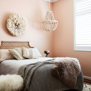 Inspiration for a contemporary bedroom in Sydney with pink walls, medium hardwood floors and brown floor.
