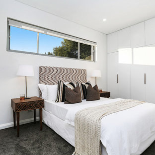 Contemporary guest bedroom in Sydney with white walls, carpet and grey floor.