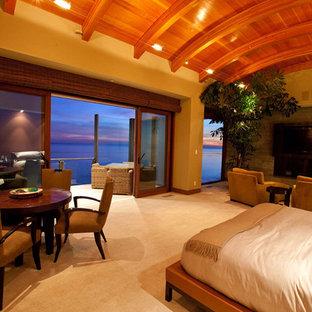 Modelo de dormitorio tipo loft, costero, extra grande, con paredes beige, suelo de baldosas de cerámica, chimenea tradicional y marco de chimenea de hormigón