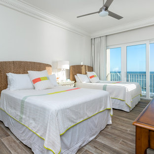 Bedroom - mid-sized beach style guest medium tone wood floor and brown floor bedroom idea in Other with white walls and no fireplace