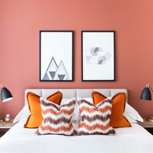Contemporary bedroom in London with orange walls.