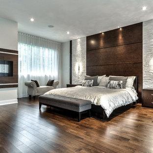 Geräumiges Modernes Hauptschlafzimmer mit Kamin und Kaminumrandung aus Holz in Montreal
