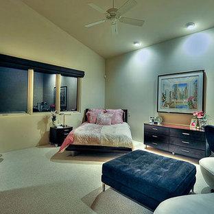 Imagen de habitación de invitados actual, grande, sin chimenea, con paredes beige, marco de chimenea de metal, moqueta y suelo beige