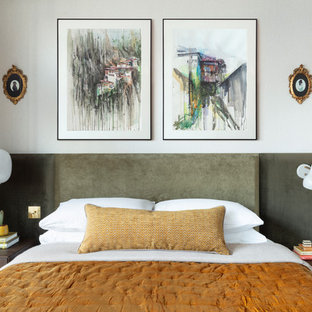 Design ideas for a contemporary bedroom in London with white walls, medium hardwood flooring and brown floors.