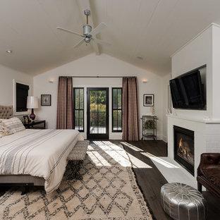 ロサンゼルスの広いコンテンポラリースタイルのおしゃれな主寝室 (白い壁、濃色無垢フローリング、標準型暖炉、レンガの暖炉まわり、茶色い床) のレイアウト