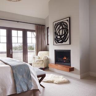 Стильный дизайн: хозяйская спальня среднего размера в современном стиле с бежевыми стенами, ковровым покрытием, стандартным камином и фасадом камина из штукатурки - последний тренд