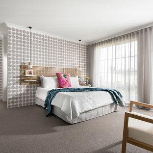 На фото: хозяйская спальня среднего размера в современном стиле с разноцветными стенами, ковровым покрытием и серым полом с