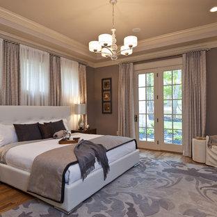 Immagine di una camera da letto design con pareti grigie e pavimento in legno massello medio