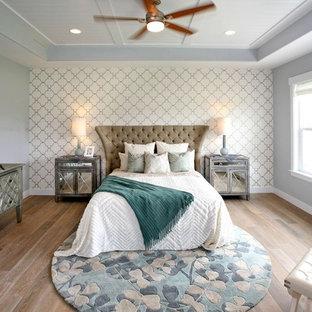 Foto de dormitorio principal, tradicional renovado, grande, sin chimenea, con paredes grises, suelo de madera en tonos medios y suelo marrón