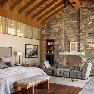 Trendy dark wood floor bedroom photo in Seattle with beige walls, a standard fireplace and a stone fireplace