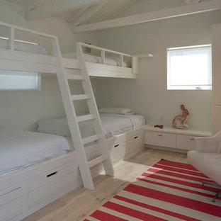 Inspiration pour une chambre d'amis design avec un mur blanc, un sol en bois clair et aucune cheminée.