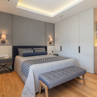 Mid-sized trendy master medium tone wood floor and brown floor bedroom photo in New York with gray walls and no fireplace