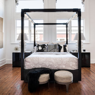 Large contemporary loft-style bedroom in Melbourne with white walls, brown floor and light hardwood floors.