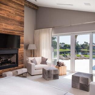 Immagine di una camera da letto design con pareti grigie, moquette, camino classico e cornice del camino in legno