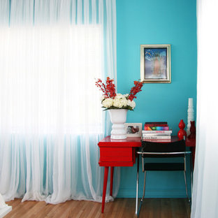 Inspiration for a contemporary medium tone wood floor bedroom remodel in Miami with blue walls