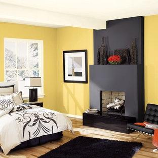 Idéer för ett modernt huvudsovrum, med gula väggar och ljust trägolv