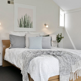 Inspiration for a contemporary bedroom in Hobart with white walls and black floor.