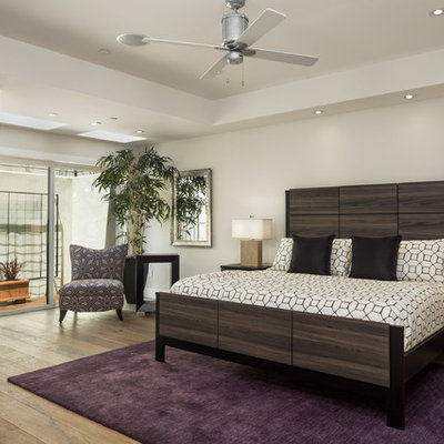 Trendy master light wood floor bedroom photo in Other with white walls
