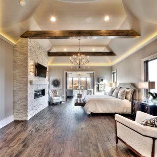 Idée de décoration pour une très grand chambre parentale design avec un mur gris, un sol en bois brun, une cheminée ribbon et un manteau de cheminée en pierre.