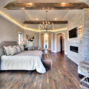 Inspiration för ett funkis huvudsovrum, med grå väggar, mellanmörkt trägolv, en bred öppen spis och en spiselkrans i sten